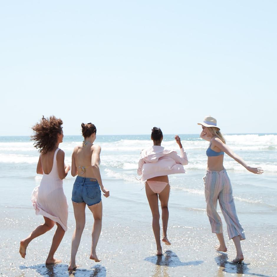 Women frolic on beach wearing Lightbox jewelry.