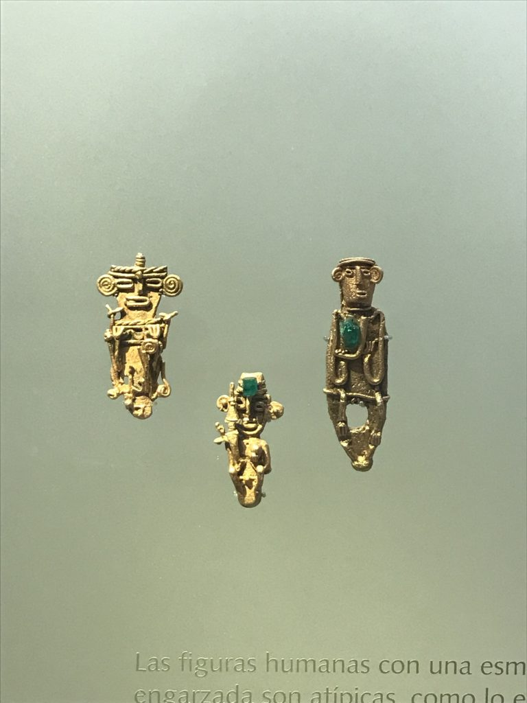 Human gold figures with emeralds